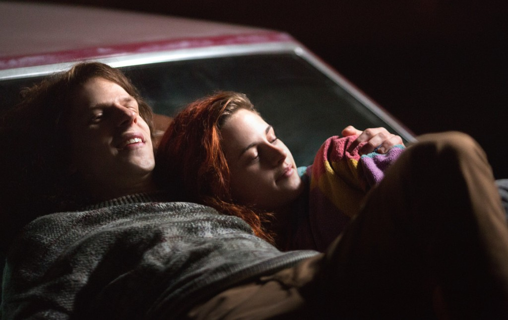 jessie eisenberg and kristen stewart laying on a car in american ultra