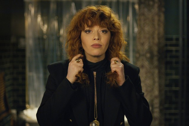 Natasha Lyonne looking in a mirror and pulling her hair in Russian Doll