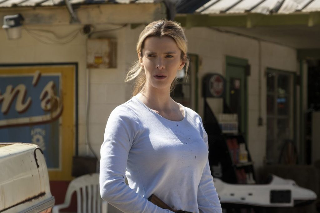 Betty Gilpin holding a gun outside of a gas station in The Hunt