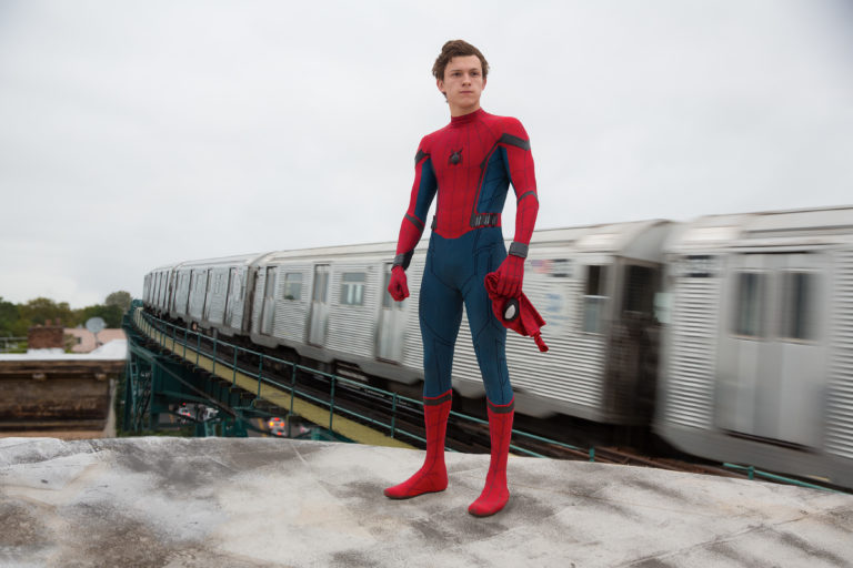 Tom Holland as Peter Parker with his Spider-Man mask off beside a subway car