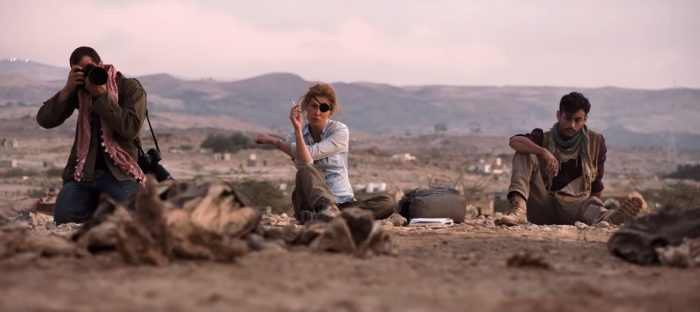 Rosamund Pike as Cat Colvin with eye patch smoking a cigarette in Syria with Jamie Dorman taking a picture in A Private War