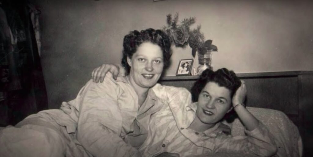 Terry Donahue and Pat Henschel as young adults posing in bed