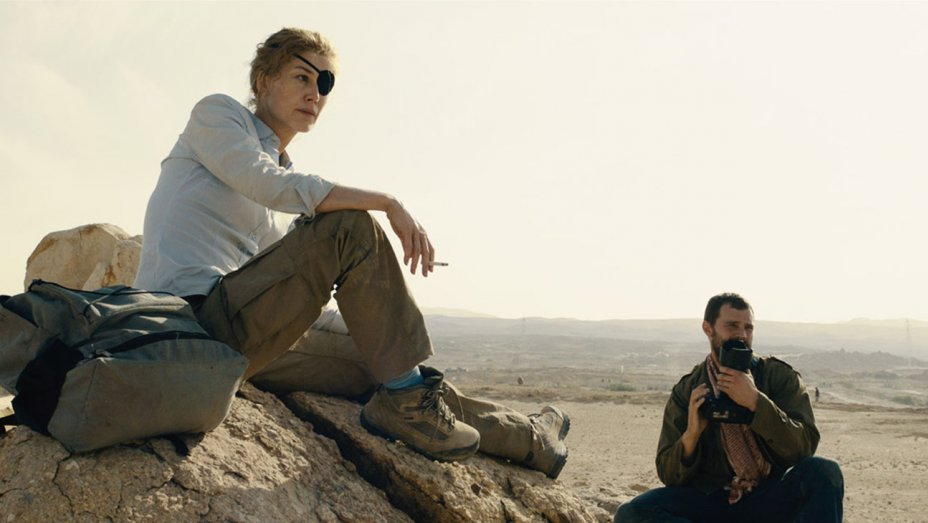 Rosamund Pike as Cat Colvin with eye patch in Syria and Jamie Dorman with a camera in A Private War