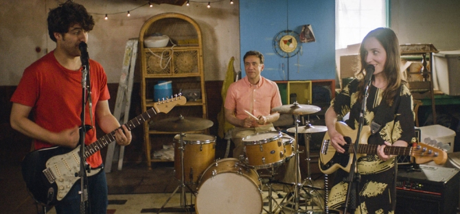 Zoe Lister-Jones, Frank Armisen, and Adam Pally playing instruments in Band Aid