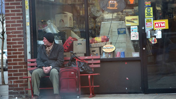 Richard Gere sitting outside of convenient store in Time Out of Mind