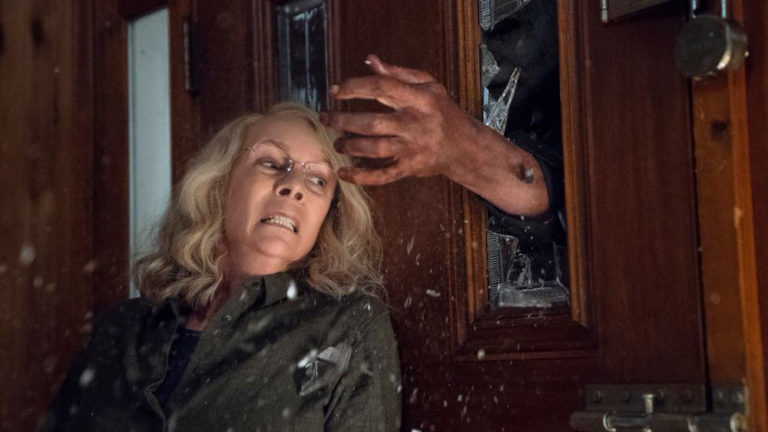 michael myers breaking window to get to laurie strode (jamie lee curtis) in halloween 2018