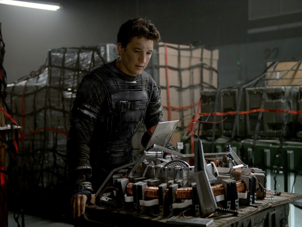miles teller examining a machine in fantastic 4