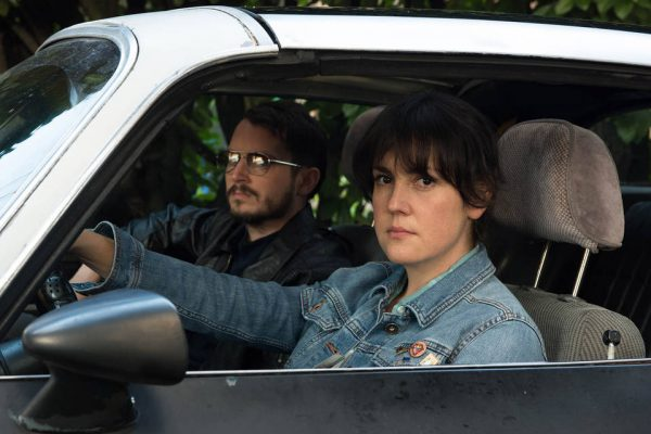 Melanie Lynskey and Elijah Wood sitting in a car in i don't feel at home in this world anymore movie