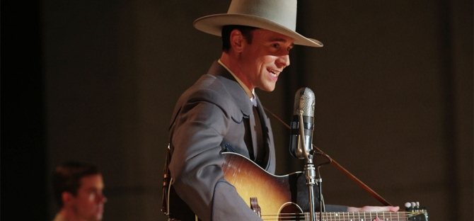 Tom Hiddleston as Hank Williams playing the guitar with a cowboy hat