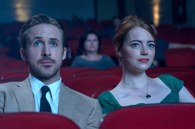emma stone and ryan gosling sitting in a theater in la la land movie