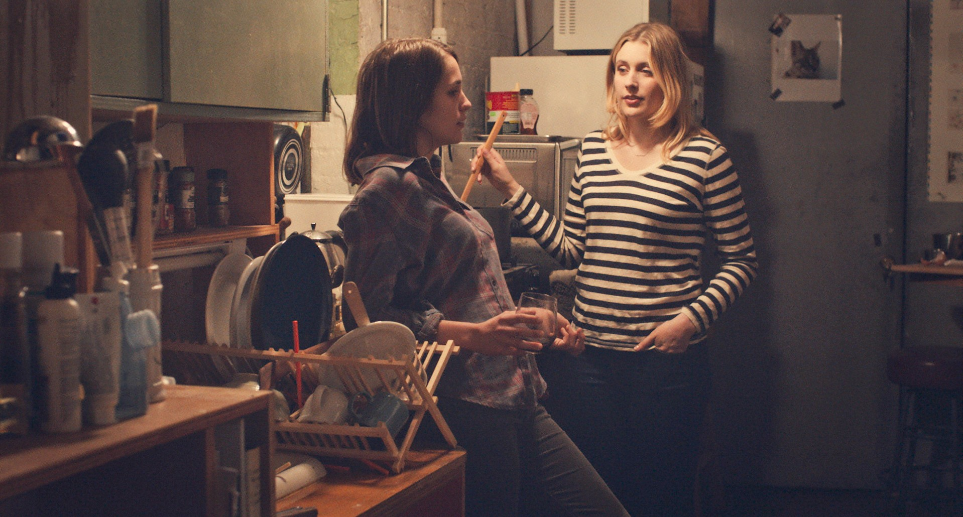 Lola Kirke and Greta Gerwig sitting together in the kitchen in Mistress America