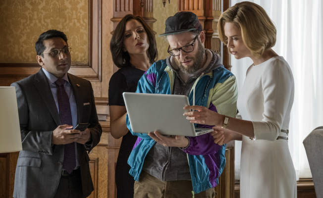 Seth Rogen, Charlize Theron, and June Diane Raphael looking at a laptop computer in The Long Shot