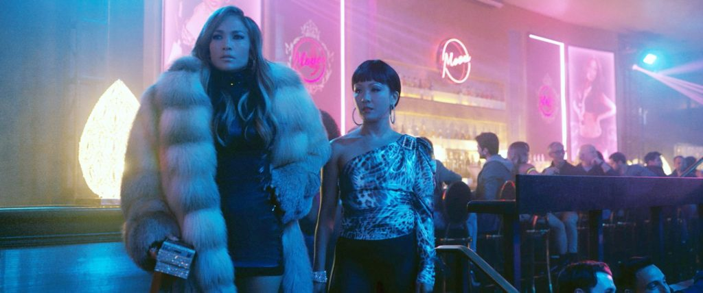 Jennifer Lopez in fur coat showing Constance Wu the ropes in Hustlers