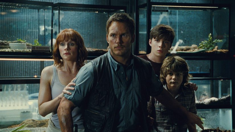 Chris Pratt standing between the dinosaurs and kids in Jurassic World