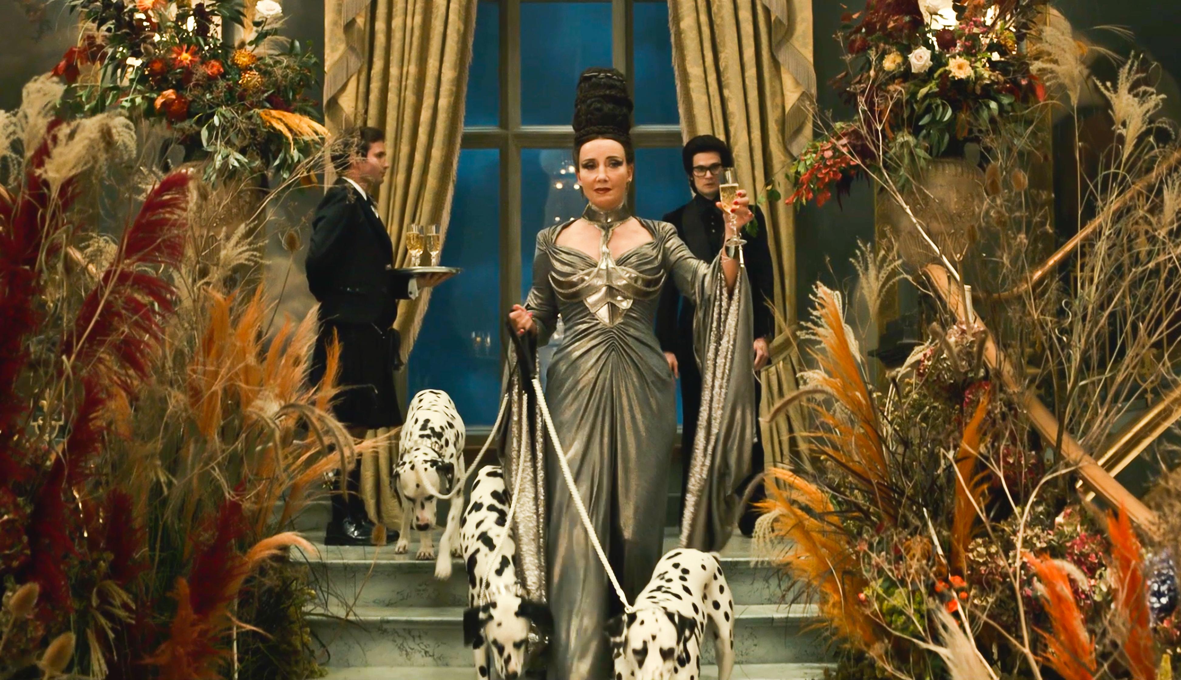 Emma Thompson holding dalmatians in Cruella movie